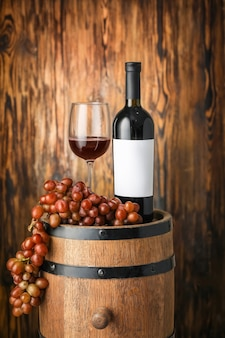 Bottle of red wine, glass and grapes on wooden barrel