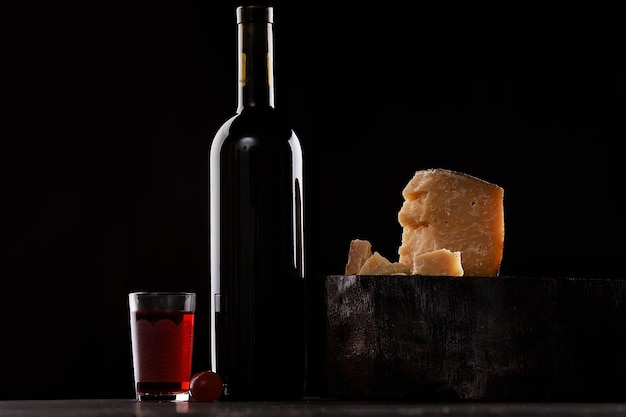 A bottle of red wine and a glass of red wine, an expensive sort of cheese with mold and grapes. on black background. place for logo.