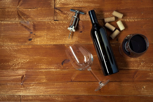 Bottle of red wine and glasses with corkscrew