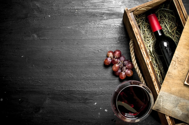 Bottle of red wine in an old box with a branch of grapes on the black chalkboard