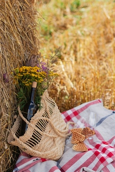 Bottle of red wine, two glasses and wildflowers in basket on the field and sheaf.