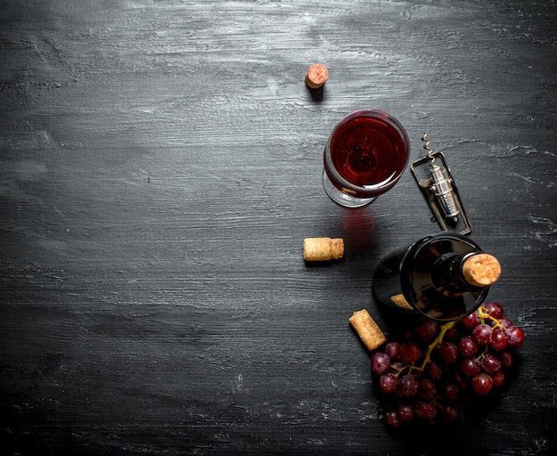 Bottle of red wine with a corkscrew on a black wooden background