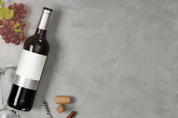 Bottle of red wine with label. glass of wine and grape. wine bottle mockup. top view.