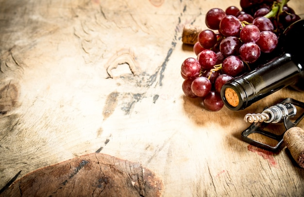 Bottle of red wine with a sprig of grapes and a corkscrew on wooden background