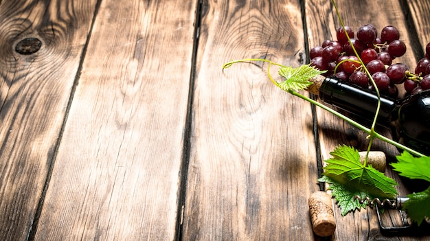 Bottle of red wine with a sprig of grapes. on a wooden table.