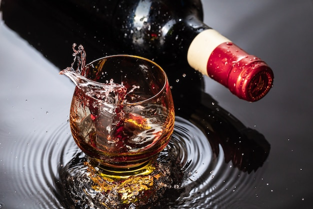 Bottle of red wine with wineglass. water splash and droplet on the black reflection.