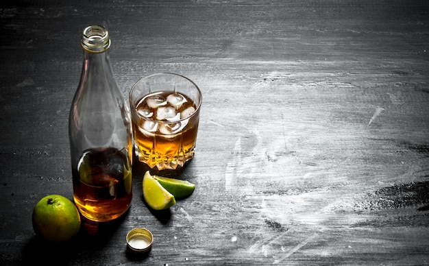 Bottle of rum with lime. on a black wooden background.