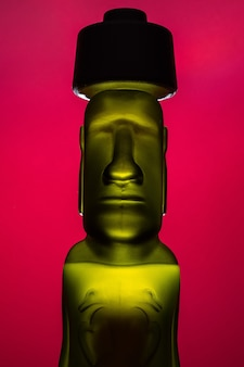 Bottle or sculpture of green and yellow color humanoid moai isolated on red background, rapanui