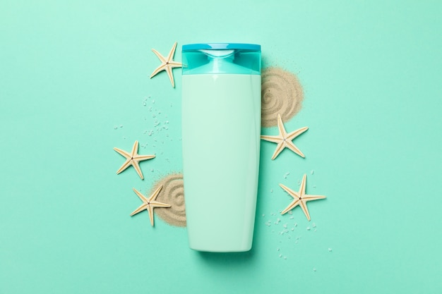Bottle of shampoo, starfishes and sand on mint background