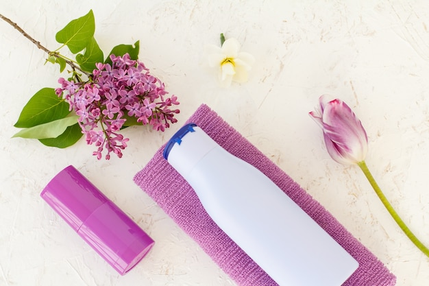 Bottle of shampoo, a towel, deodorant, tulip and lilac flowers on the structured background. women's cosmetics and accessories. top view.
