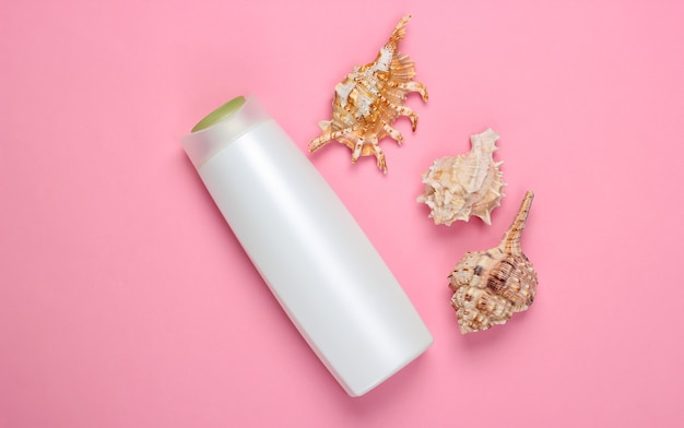 Bottle of shampoo with minerals and sea shells on a pink. hair care
