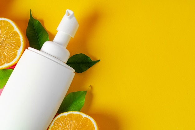Bottle of skincare cosmetics with sliced lemons background