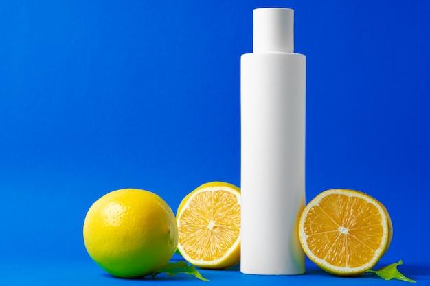 Bottle of skincare cosmetics with sliced lemons