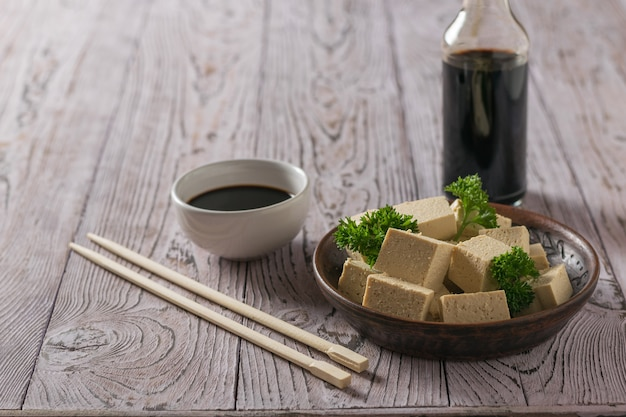 A bottle of soy sauce and slices of tofu cheese on a wooden table. soy cheese. vegetarian product.