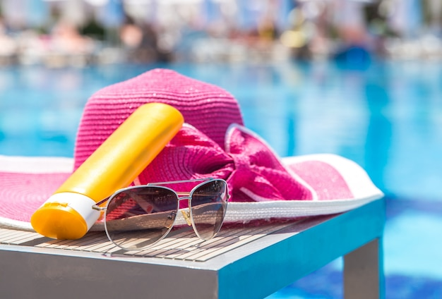 Bottle of sun cream, hat and sunglasses next to swimming pool in hotel
