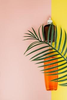 Бутылка солнцезащитный крем на ярком квадратном желто-розовом фоне