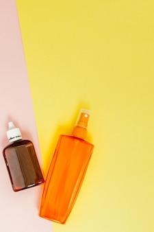 明るい正方形の黄色とピンクのボトル日焼け止め