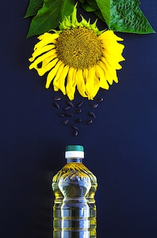 Bottle of sunflower oil, flower and serving seeds