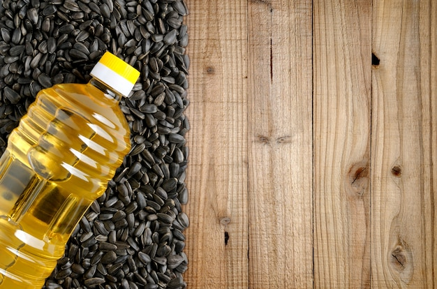 Bottle of sunflower oil and sunflower seeds on wooden