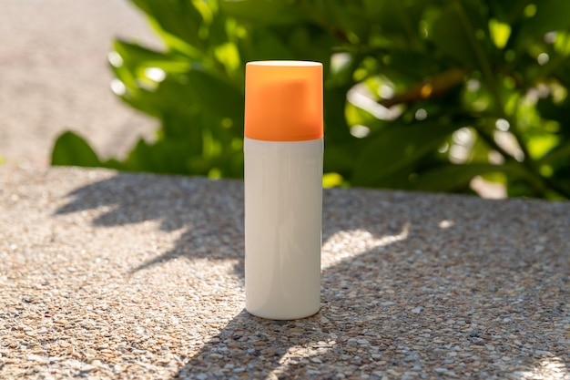Bottle of sunscreen lotion on the beach by the sea. skin care concept