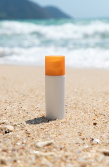 Bottle of sunscreen lotion on the sandy beach by the sea