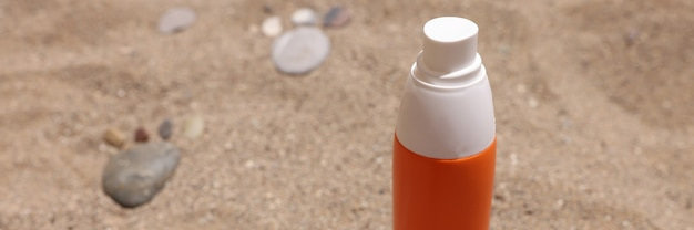 Bottle of sunscreen lotion sits on hot sand