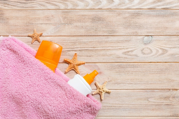 A bottle of sunscreen, pink towel and seashells on wooden background. summer travel concept. top view with copy space.