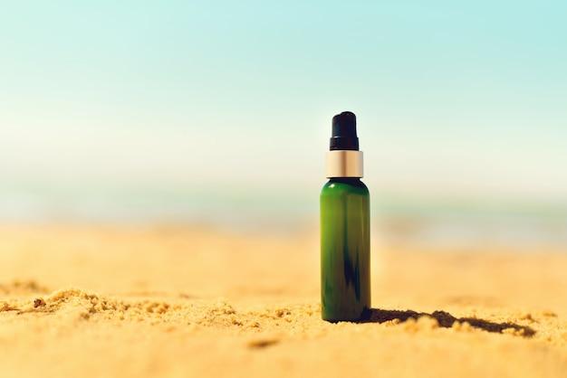 Bottle of sunscreen in sand