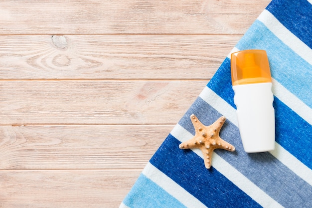 A bottle of sunscreen, striped blue towel and seashells on wooden background. summer travel concept. top view with copy space.