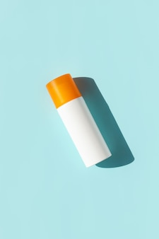 Bottle of sunscreen with deep shadows on blue surface