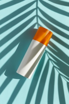 Bottle of sunscreen with palm leaf shadow on blue surface