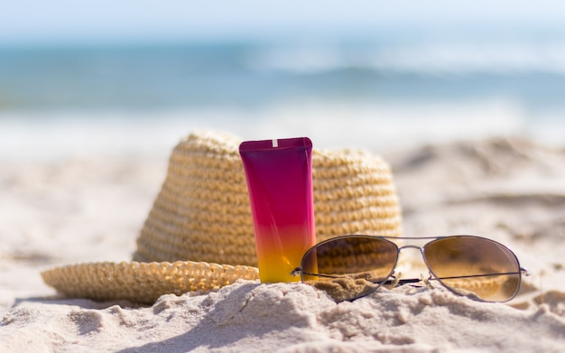 Bottle of sunscreen with sunglasses and hat on beach