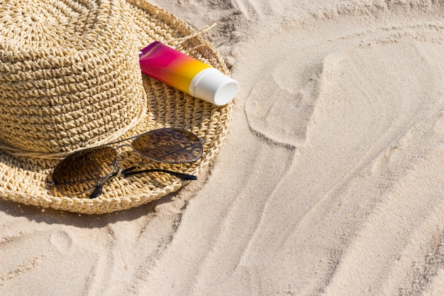 A bottle of sunscreen with sunglasses and panama hat on a beach
