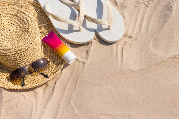 A bottle of sunscreen with sunglasses, panama hat and slipper on a beach