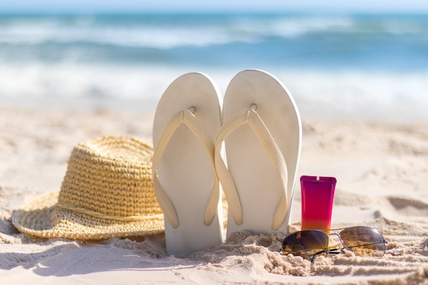 Bottle of sunscreen with sunglasses, panamhat and slipper on beach, summer skin remedies and protection