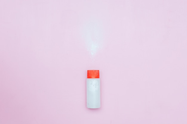 Bottle of talcum baby powder on pink background. powder spilled from white container