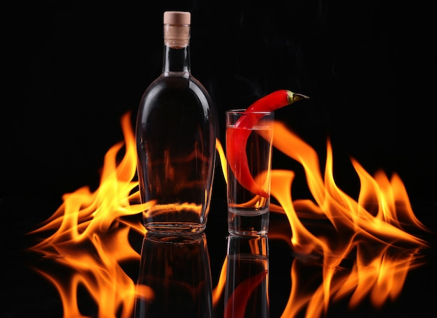 Bottle of tequila on fire and a glass with chilli pepper