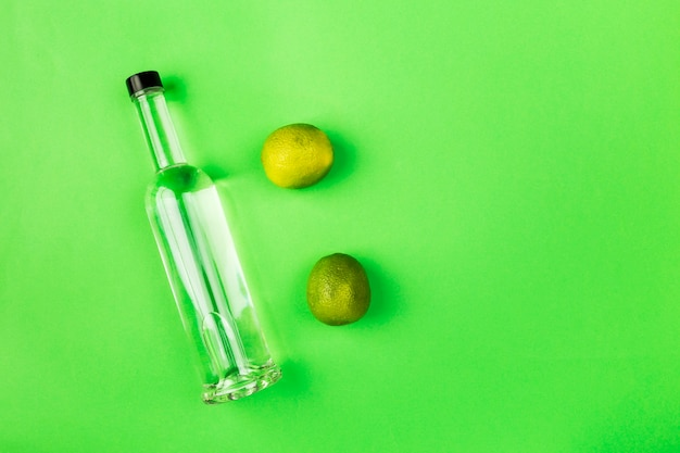 Bottle of tequila, lime on green space. top view, copy space