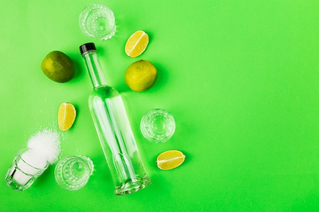 Bottle of tequila, lime, salt, shots on green space. top view, copy space