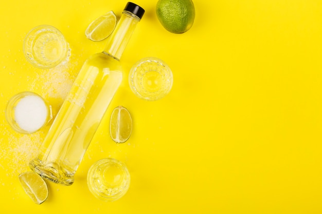 Bottle of tequila, lime, salt, shots on yellow space. top view, copy space