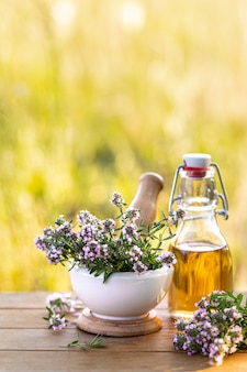 Bottle of thyme essential oil with fresh sprigs of thyme on a wooden background and nature in the background. copy space