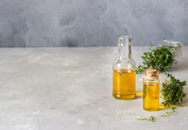 Bottle of thyme (thymus) essential oil with fresh thyme