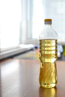 A bottle of vegetable oil on the table in the kitchen is