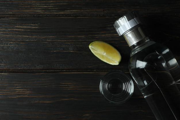 Bottle of vodka, shot and lime slice on wooden table