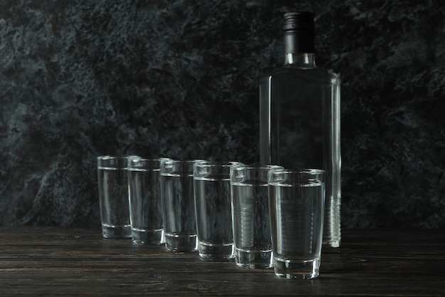 Bottle of vodka and shots on wooden table