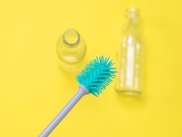노란색 벽에 브러시와 빈 병을 세척하는 병. 위생과 청결의 개념.
