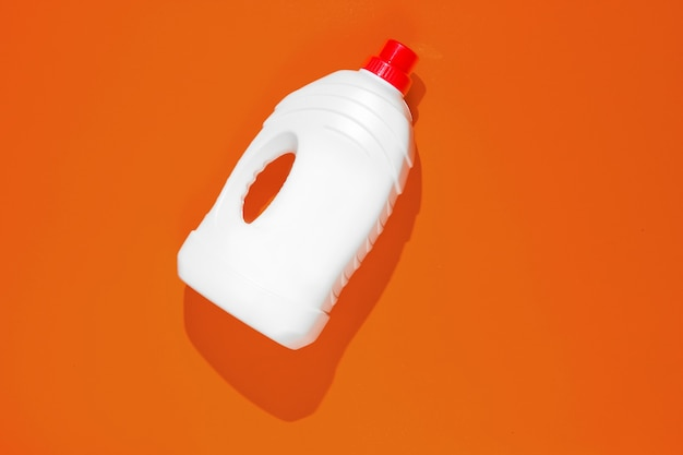 Bottle of washing gel on orange background. top view