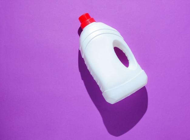 Bottle of washing gel on purple table. top view
