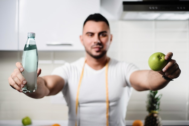 Bottle of water and an apple close-up in the hands of an athletic man in the kitchen