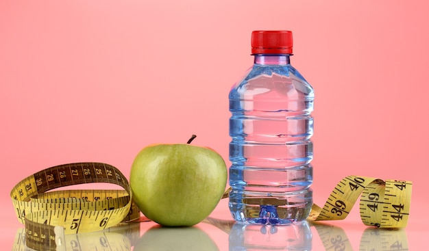 Bottle of water, apple and measuring tape on pink surface